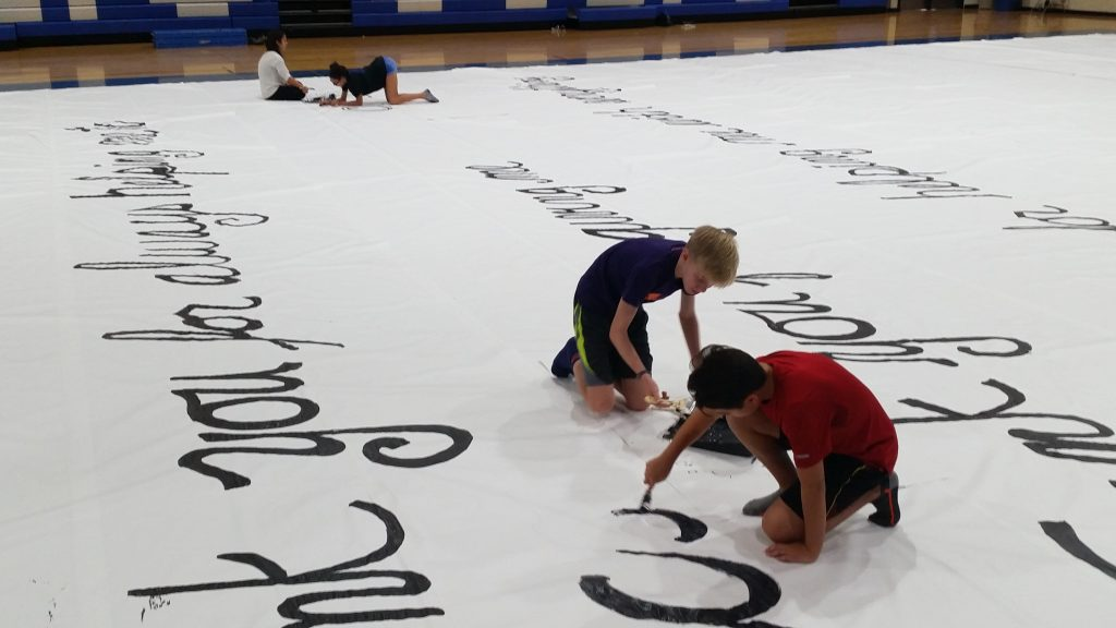 Students painting words on World's Largest Thank You Letter