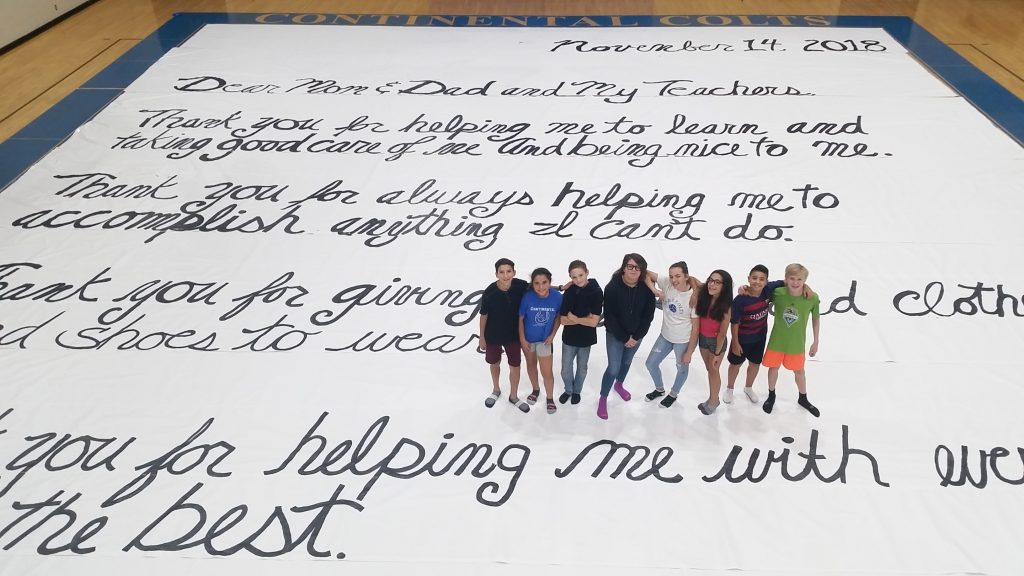 Students standing on top of World's Largest Thank You Letter