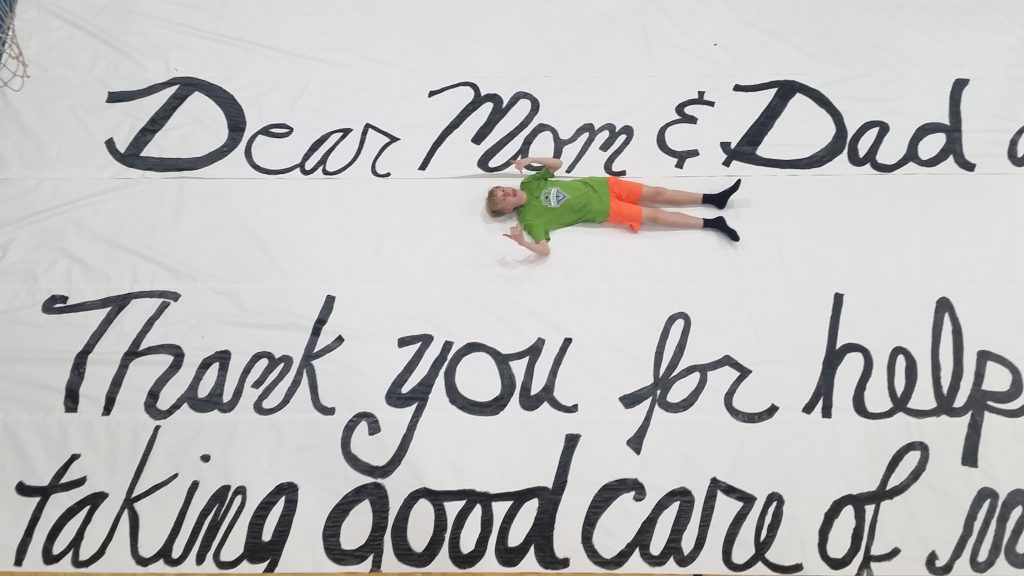 Student relaxing on World's Largest Thank You Letter